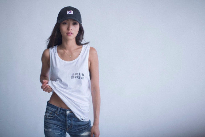 Indoor shot of female model wearing KORELIMITED's 1882 black dad hat and LA to Seoul white tank top.