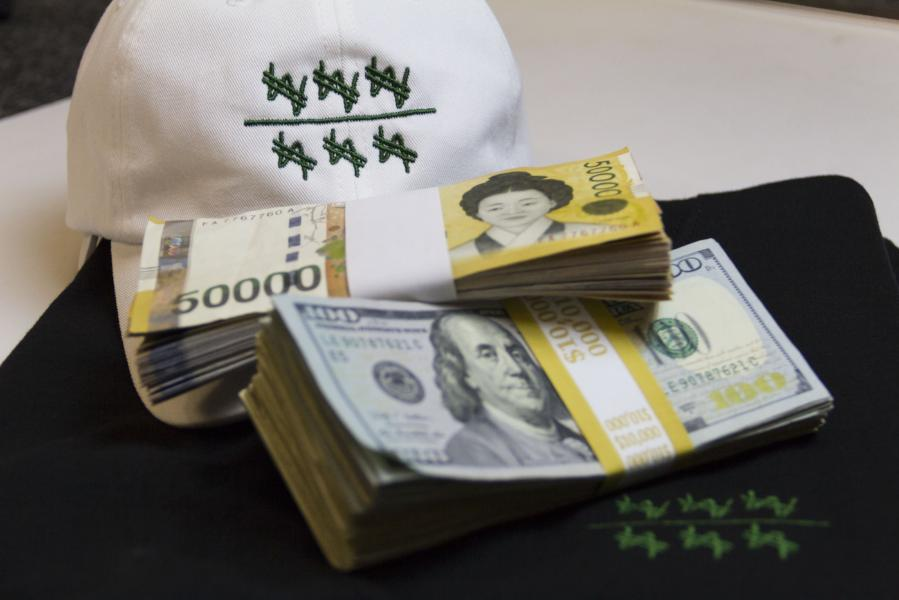 Shot of white won over dollar dad hat with real won and dollar bills.