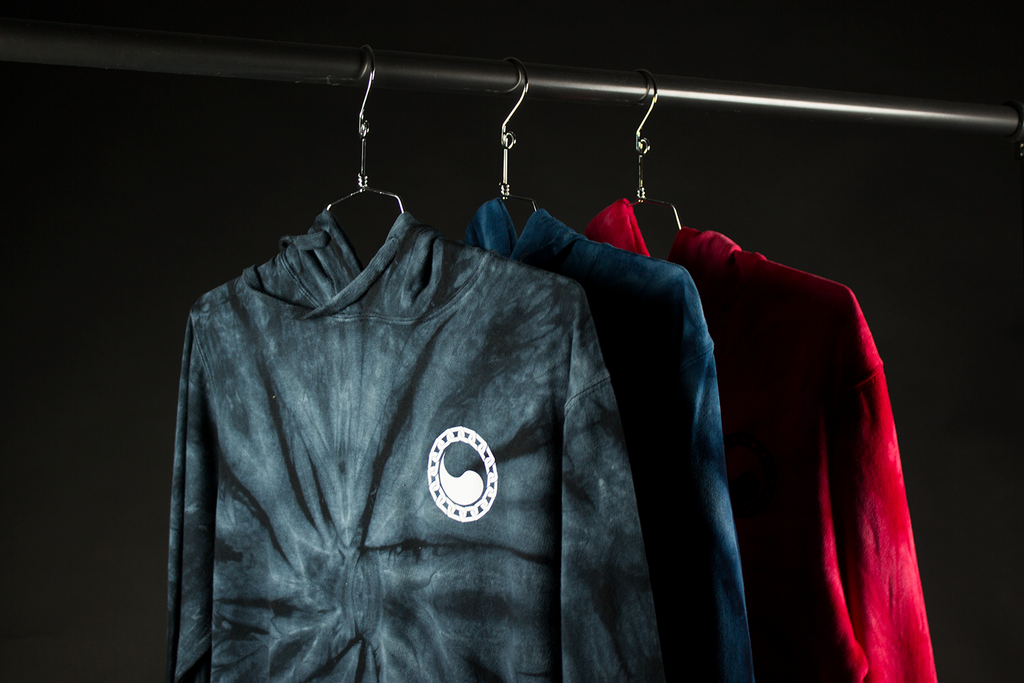 Top front shot of hanging tie dye hoodies. Displaying the black tie dye KORE Sleeved pullover hoodie with white yin and yang chest print. Also showing some navy and red tie dye hoodies.