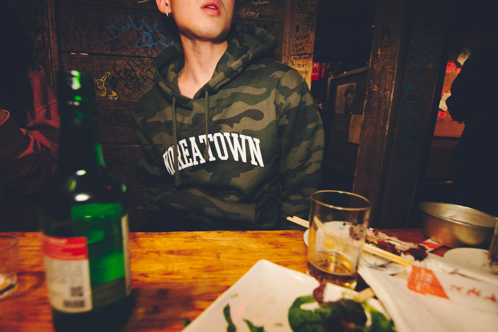 Male model wearing KOREATOWN LA pullover hoodie in forest camo at Dansungsa while drinking soju. KORE - Keepin Our Roots Eternal