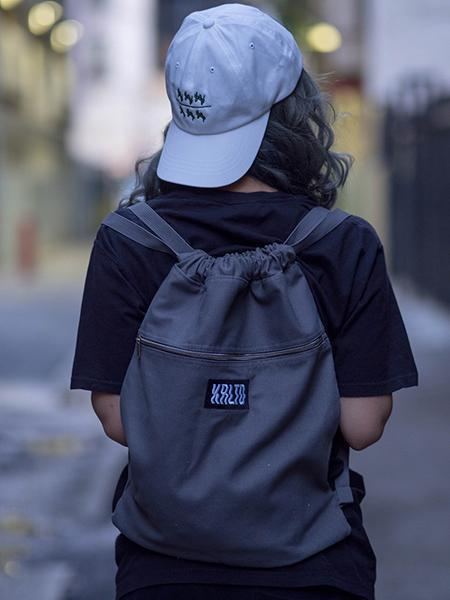 Back view shot of model wearing charcoal KRLTD backpack with white won over dollars dad hat.