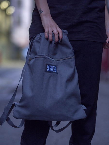 Shot of model holding charcoal KRLTD backpack.