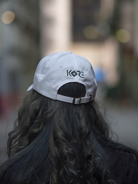 Model wearing white dad hat with green won over dollar embroidered on the front and KORE on the back.