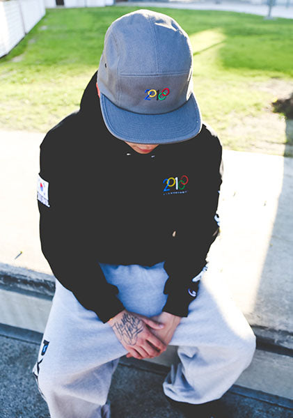 Model wearing black 2018 PC Champion hoodie, oxford grey 2018 PC Champion reverse weave sweatpants, and grey jockey cap with a modified 2018 Olympic embroidery design. KORE - Keepin Our Roots Eternal