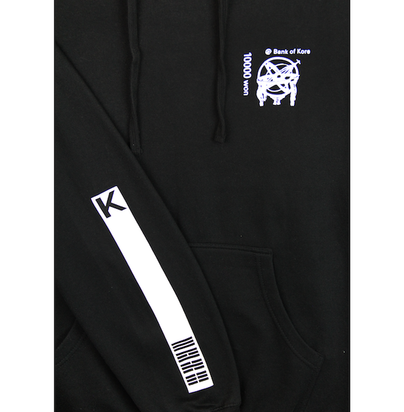 Close up view of black pullover hoodie with K and flag stripes printed on the sleeve. White Bank of KORE design is also printed on the left chest. KORE Limited - Keepin Our Roots Eternal