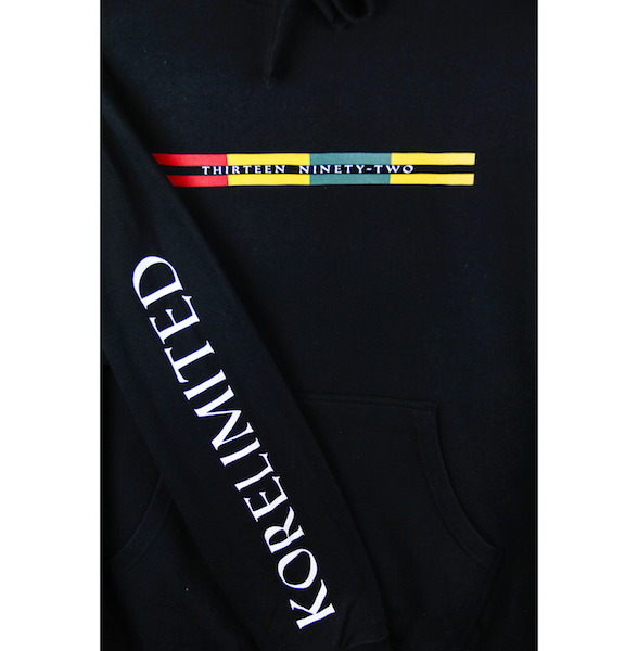 Close up view of the black pullover hoodie with Goryeo Flag colors printed on the front and KORELIMITED on the sleeves. KORE Limited - Keepin Our Roots Eternal