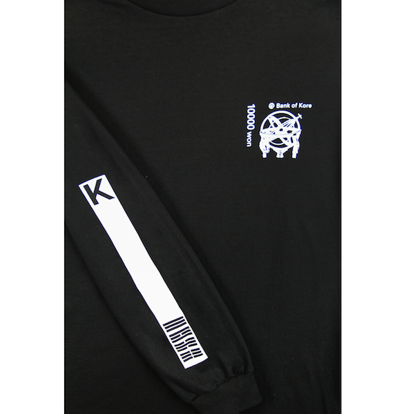 Close up view of black long sleeve with K and flag stripes printed on the sleeve. White Bank of KORE design is also printed on the left chest. KORE Limited - Keepin Our Roots Eternal