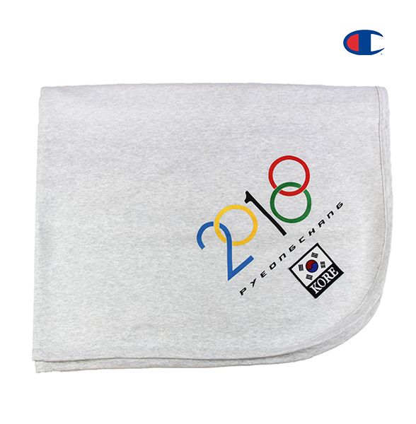 Folded light grey stadium blanket showing the 2018 and Olympic modified design on the corner along with a customized KOREA patch underneath it. KORE - Keepin Our Roots Eternal