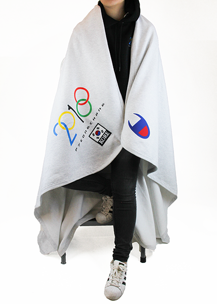 Model wrapping a light grey 2018 PC stadium blanket over the shoulders. Blanket show a 2018 and Olympic modified design with the custom KOREA patch on one corner. The other corner shows the signature C logo from Champion. KORE - Keepin Our Roots Eternal