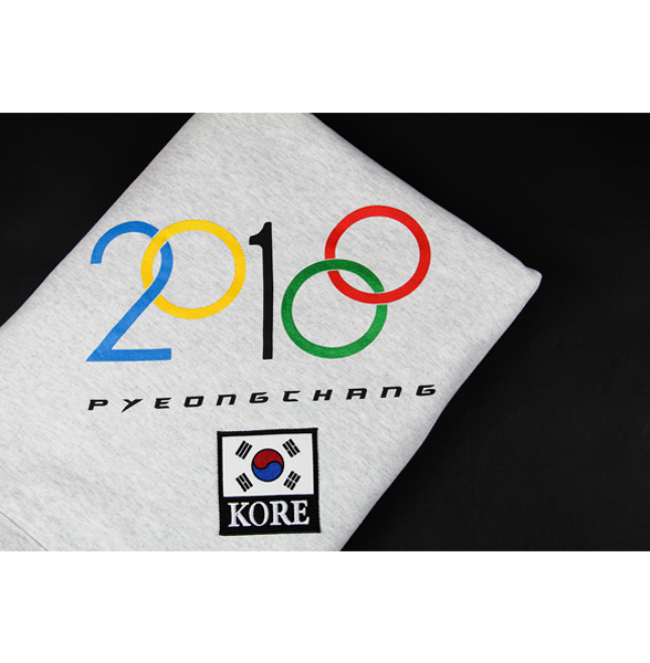 Light grey stadium blanket showing the 2018 and Olympic modified design on the corner along with a customized KOREA patch underneath it. KORE - Keepin Our Roots Eternal