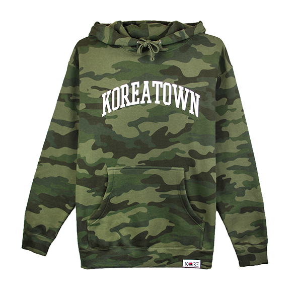 Front view photo of a forest camo pullover hoodie with KOREATOWN in arched white font. KORE - Keepin Our Roots Eternal