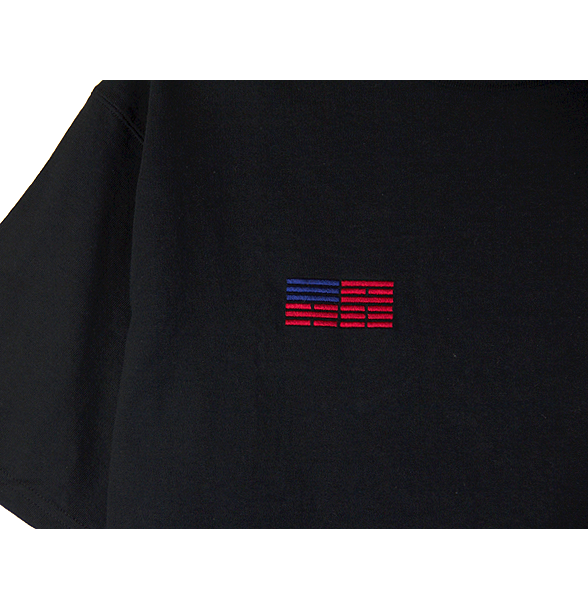 Zoomed-in front view of a black Champion jersey tee with a minimal Korean American flag embroidered over the right chest.