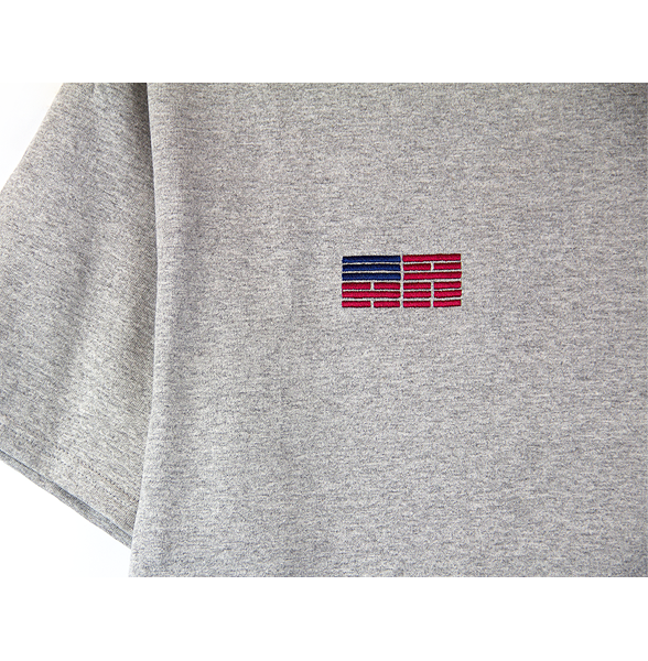 Zoomed-in front view of a heather grey Champion jersey tee with a minimal Korean American flag embroidered over the right chest.