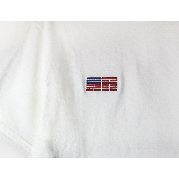 Zoomed-in front view of a white Champion jersey tee with a minimal Korean American flag embroidered over the right chest.