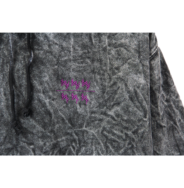 Detailed view of black acid wash hoodie with won over dollars embroidered on the chest.