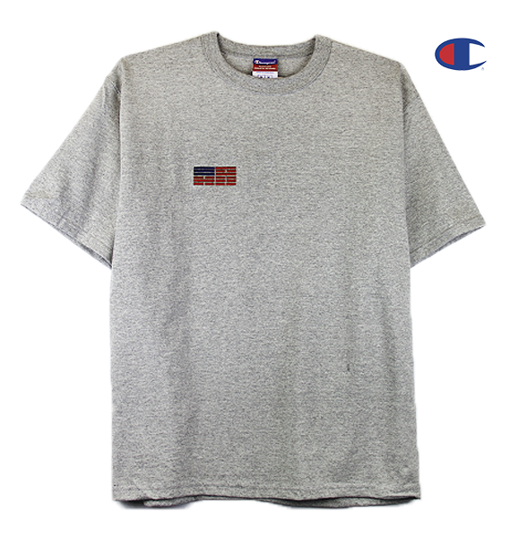 Front view of a heather grey Champion jersey tee with a minimal Korean American flag embroidered over the right chest.