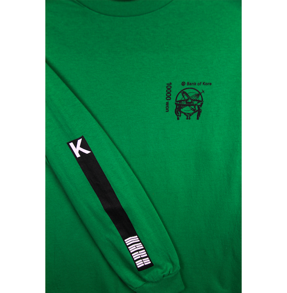 Close up view of green long sleeve with K and flag stripes printed on the sleeve. Black Bank of KORE design is also printed on the left chest. KORE Limited - Keepin Our Roots Eternal