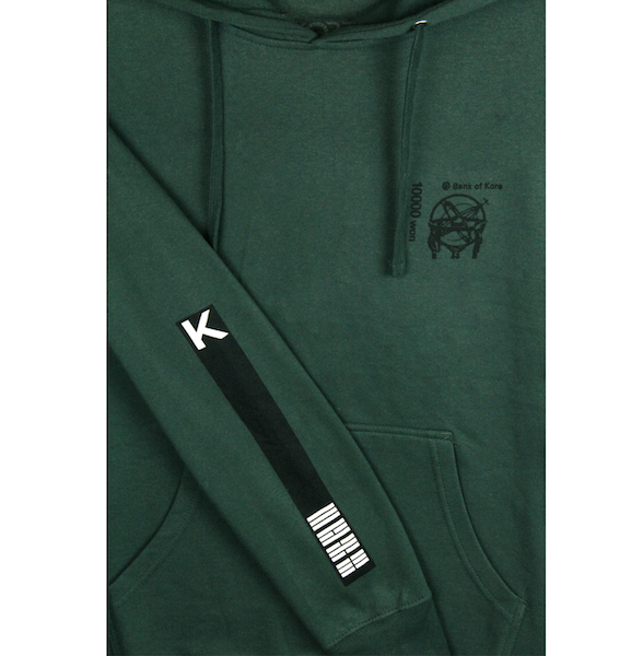 Close up view of green pullover hoodie with K and flag stripes printed on the sleeve. Black Bank of KORE design is also printed on the left chest. KORE Limited - Keepin Our Roots Eternal