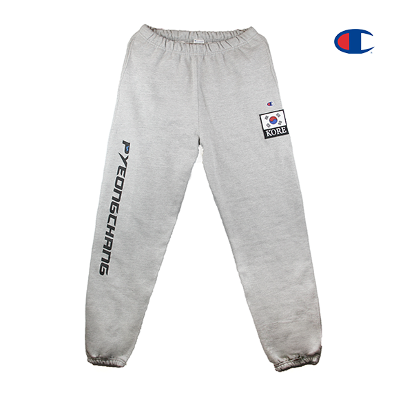 Front view of Champion reverse weave sweatpants in heather grey. Printed with a custom 2018 and Olympics design on the left side and a special KOREA patch on the right side. KORE - Keepin Our Roots Eternal