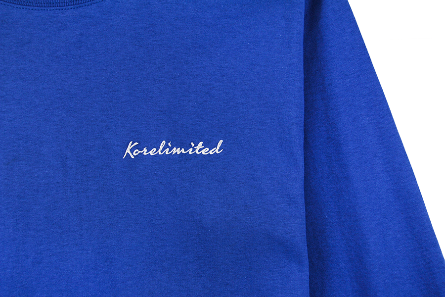 Zoomed in shot of Korelimited Script embroidery on royal blue.