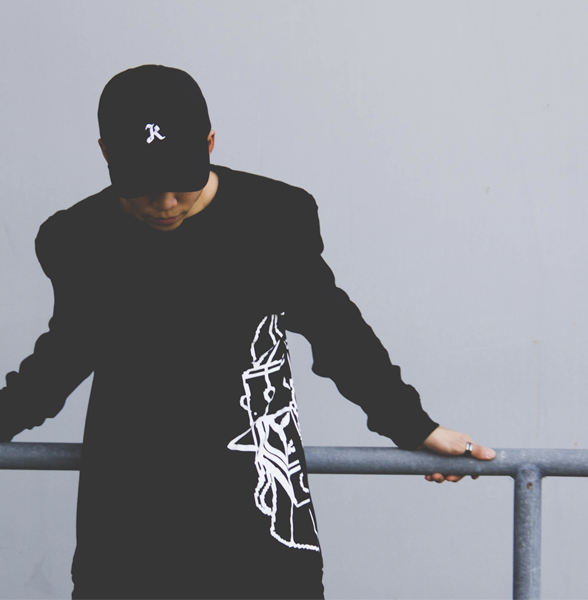 Male model wearing black Klassic K dad hat and black Champion long sleeve with half of Taekwon V head printed.