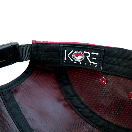 Zoomed in view of the KORE patch inside the maroon jockey cap.