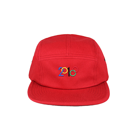 Front view of modified 2018 design with blue, yellow, black, red, and green embroidery on a red jockey cap. KORE - Keepin Our Roots Eternal