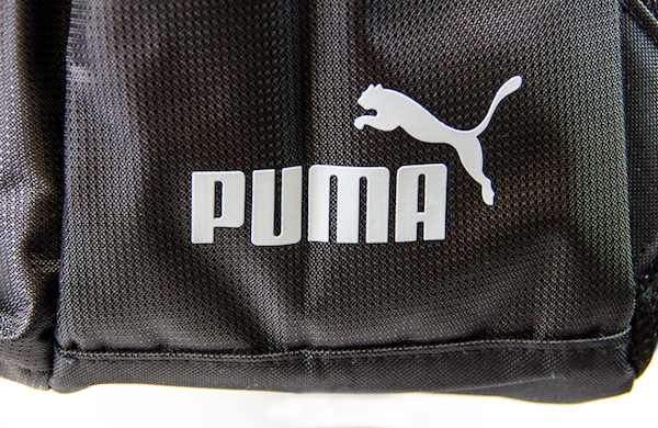 Close up view of PUMA logo print from side bottom of black backpack. KORE Limited - Keepin Our Roots Eternal