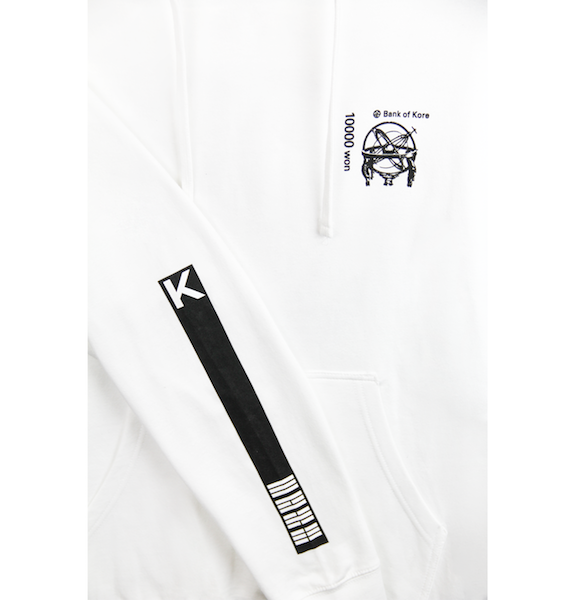 Close up view of white pullover hoodie with K and flag stripes printed on the sleeve. Black Bank of KORE design is also printed on the left chest. KORE Limited - Keepin Our Roots Eternal
