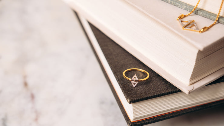 Studded Symmetry Ring in Gold on a Book