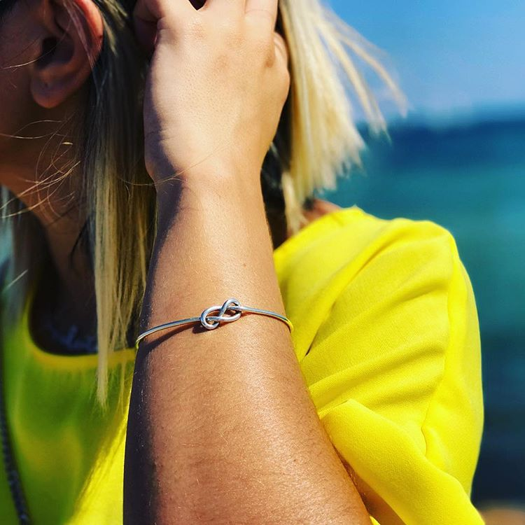 Sterling Silver Designer Model in yellow shirt wearing the Sterling Silver Knot Bracelet  by Designers Abreme Despacio on IndieFaves
