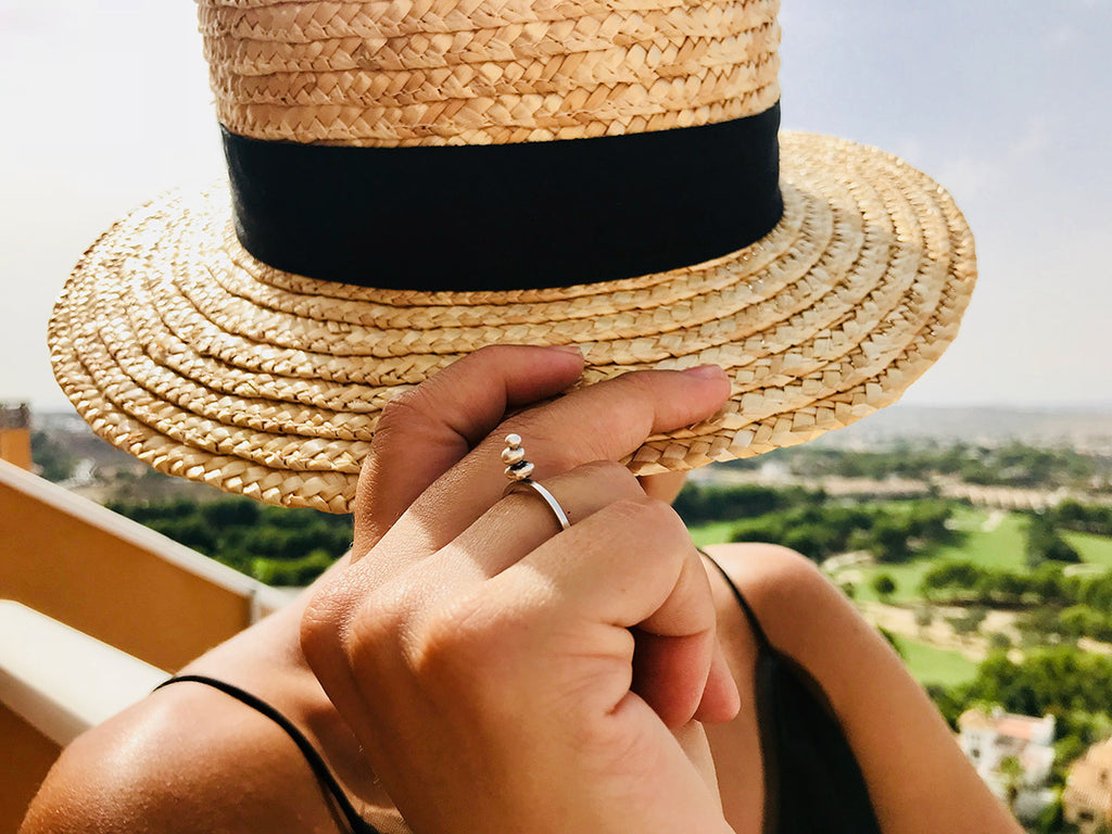 Model in straw hat wearing the Sterling Silver Zen Ring by designer Abreme Despacio on IndieFaves