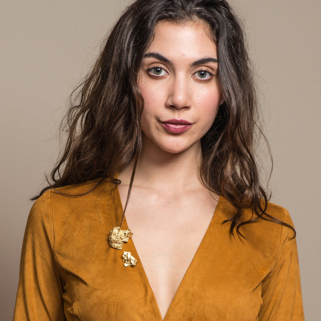 Model in a V-neck suede dress showcasing the 18K Gold-Plated Brass Large Fluorita Designer Brooch on IndieFaves