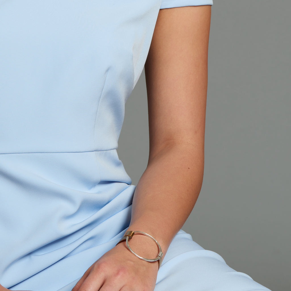 Model in blue dress wearing Sterling Silver and Bronze Open Circle Designer Bracelet on IndieFaves
