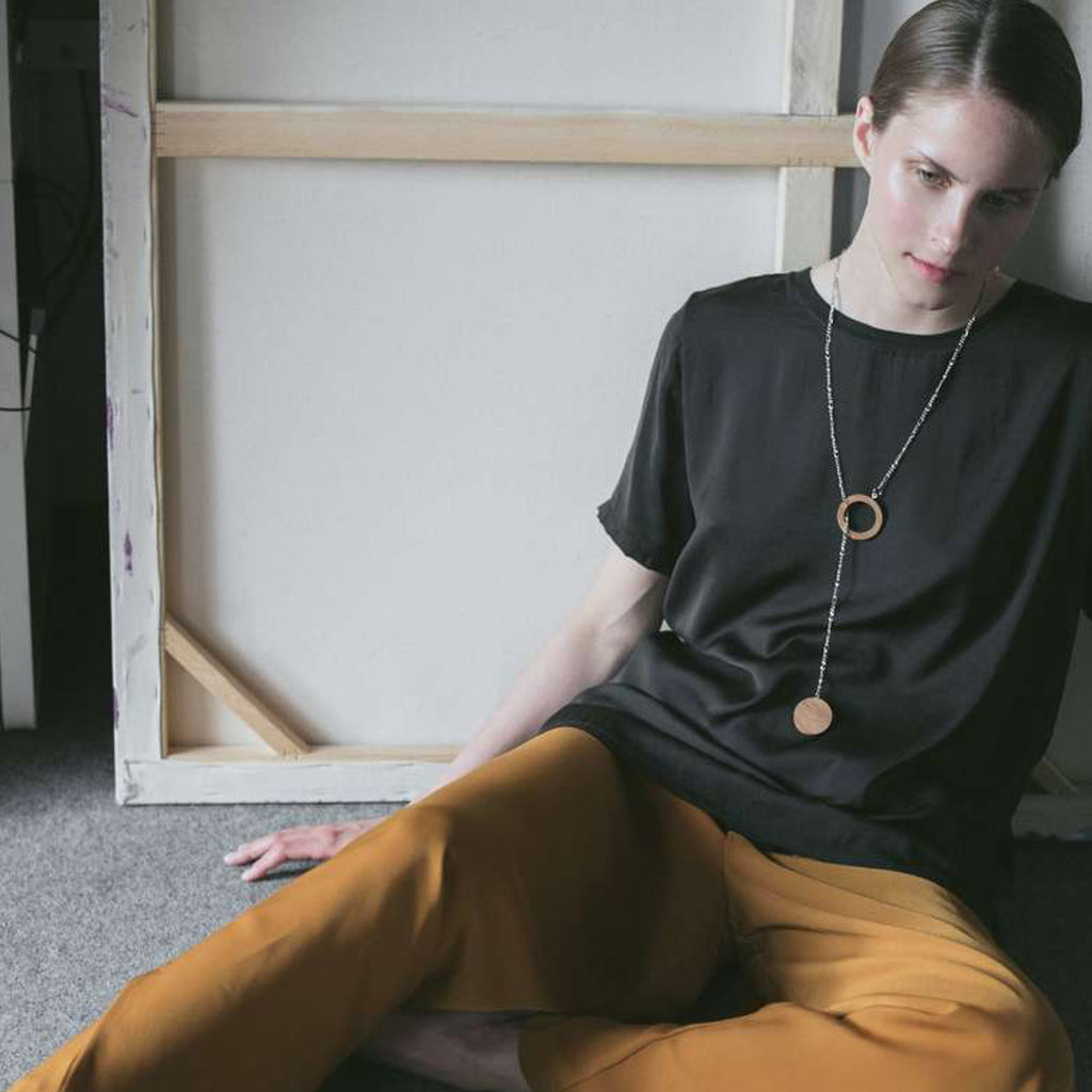 Model in black blouse wearing Sustainable BirchWood Wooden Deform Designer Necklace with Chain on IndieFaves