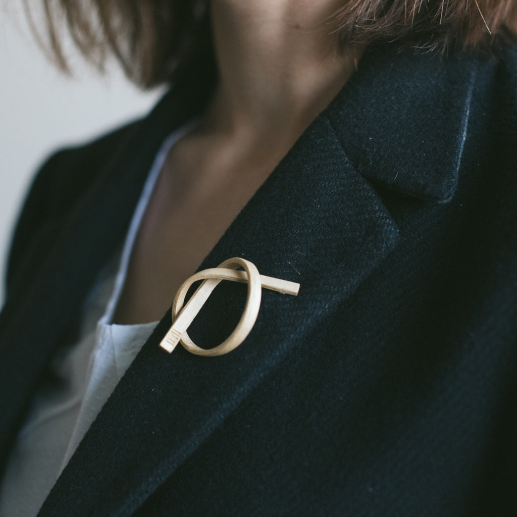 Model in black coat wearing Sustainable AshWood Wooden Alpha Designer Brooch on IndieFaves
