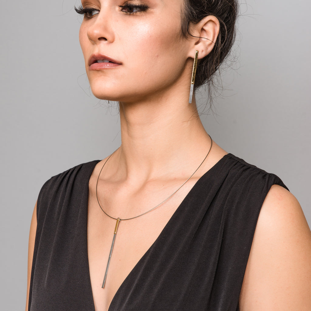 Model in a black gown wearing Upcycled Steel and Gold-Coated Dangle Designer Earrings on IndieFaves