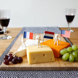 Astronaut food flags stuck in brie, cheddar and red Leicester on a cheese board with grapes.