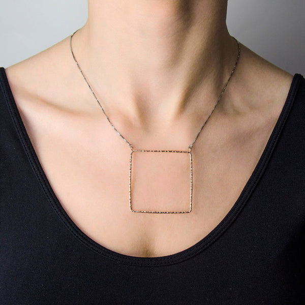 NICOLA Geometric square pendant on a long sterling silver necklace.