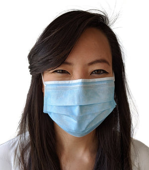 A woman modeling a blue disposable surgical face mask with white edges.