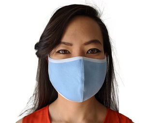 A woman modeling a blue cloth face mask with white edges.