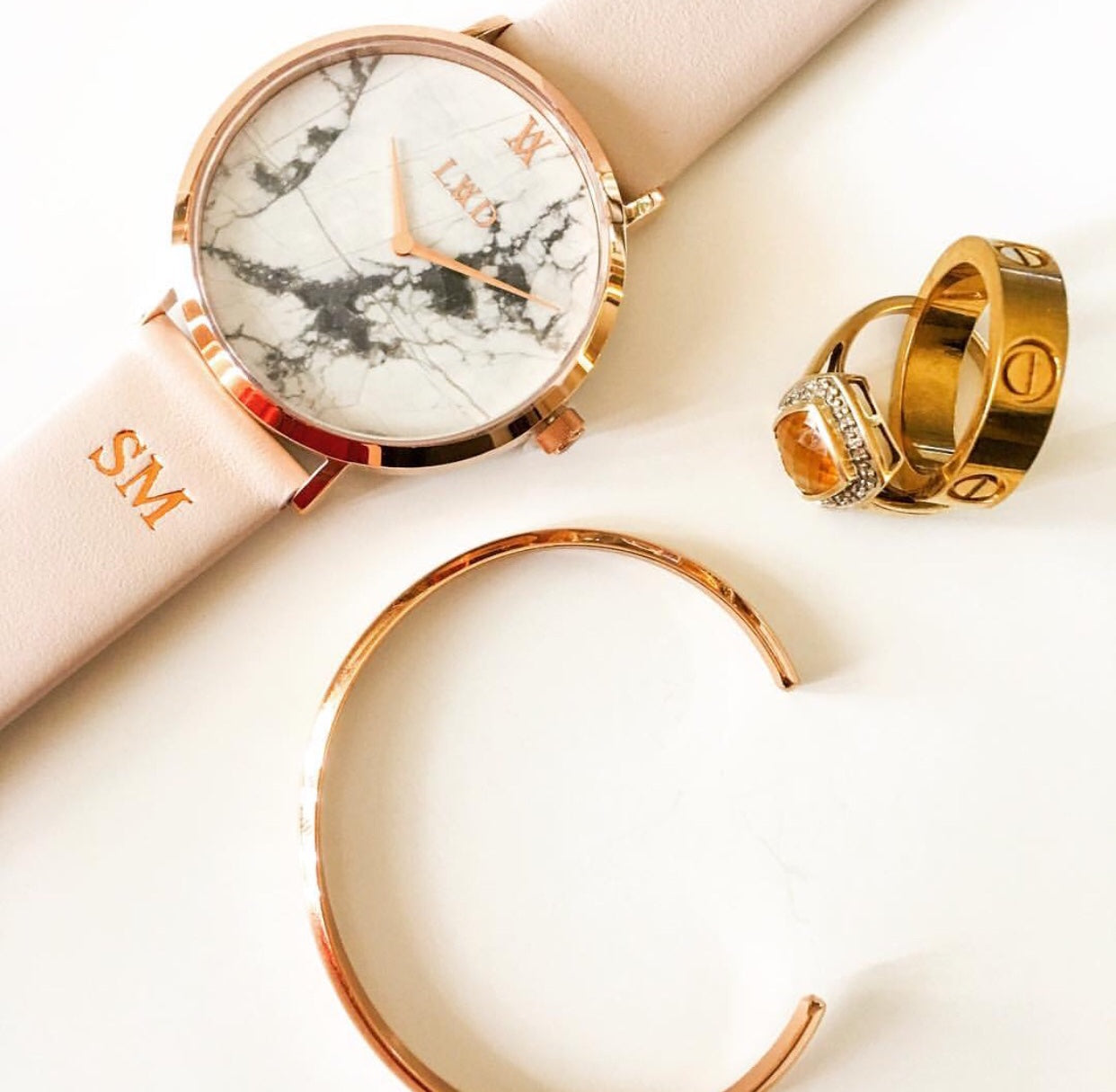 rose gold case with white marble dial watch with monogrammed nude pink strap flatlay with jewellery