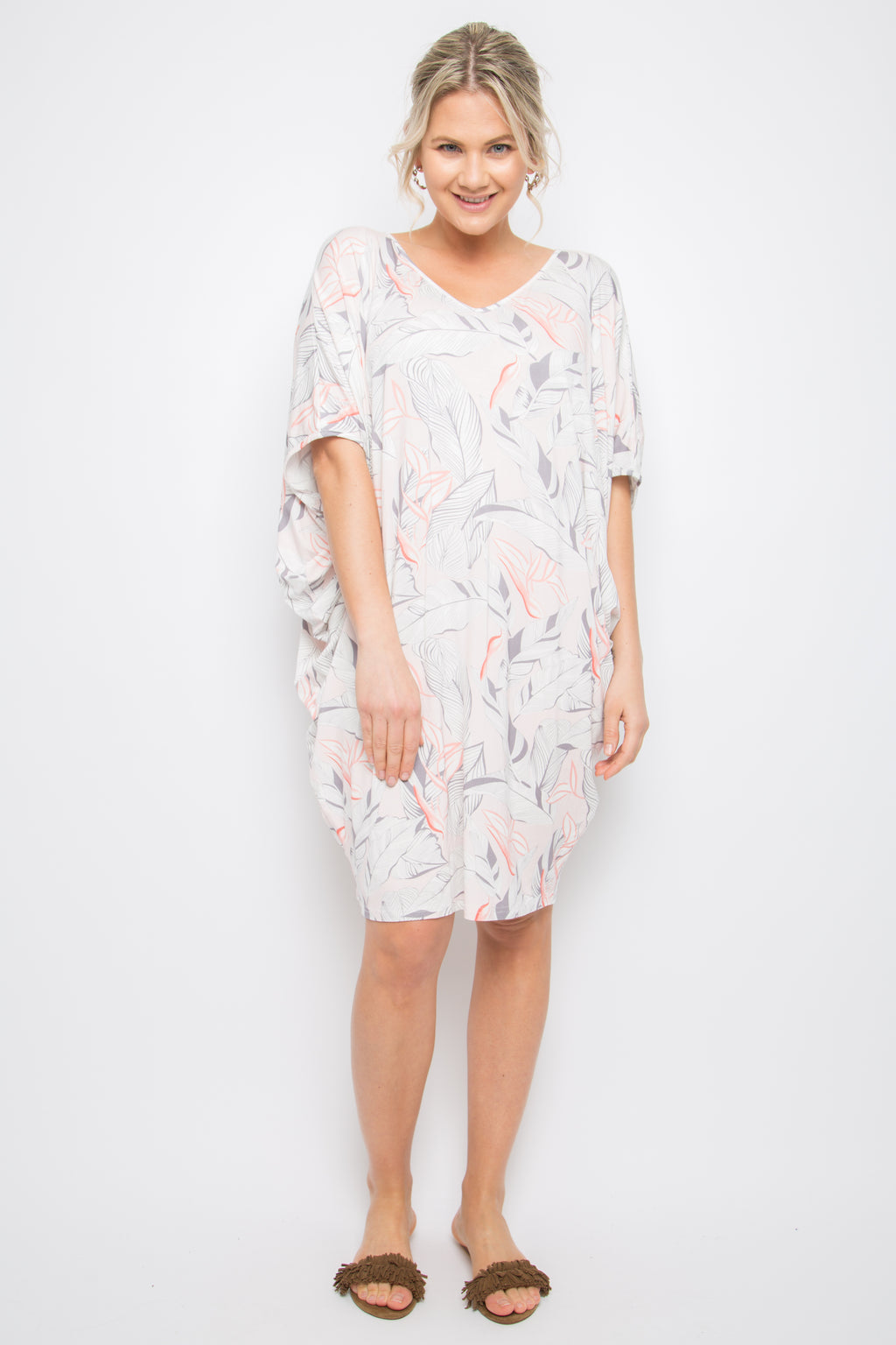 Model wears batwing dress that is white with pink and grey leafy print