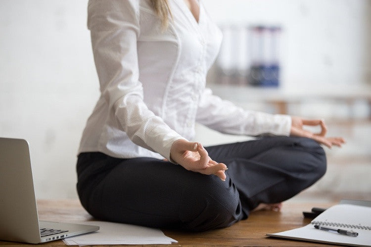 Business women sitting in yoga position