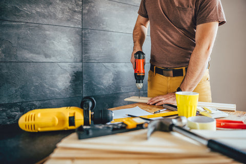 Man using power drill on a piece of wood