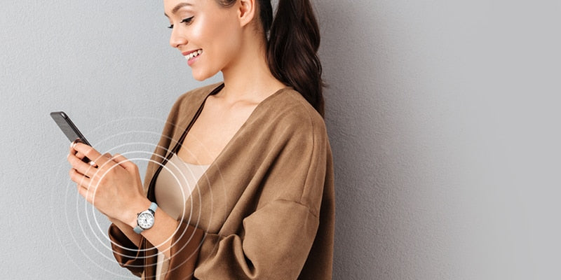 Woman wearing a Philip Stein Natural Frequency Technology watch while holding a phone