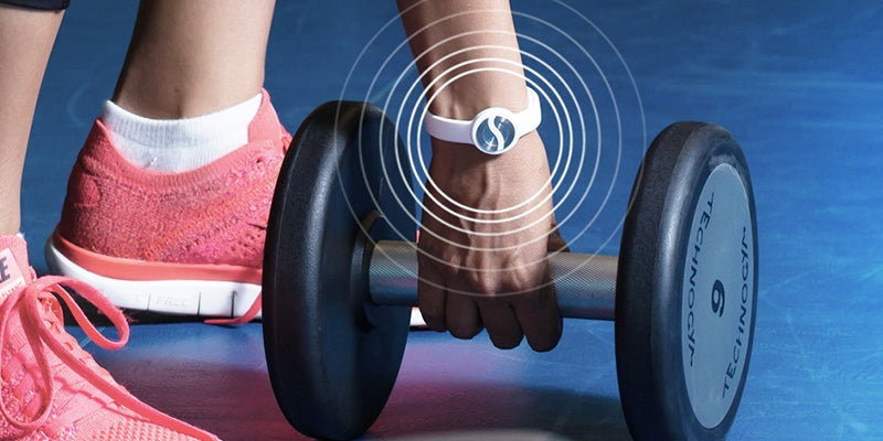 Woman picking up a dumbell while wearing a white sport bracelet