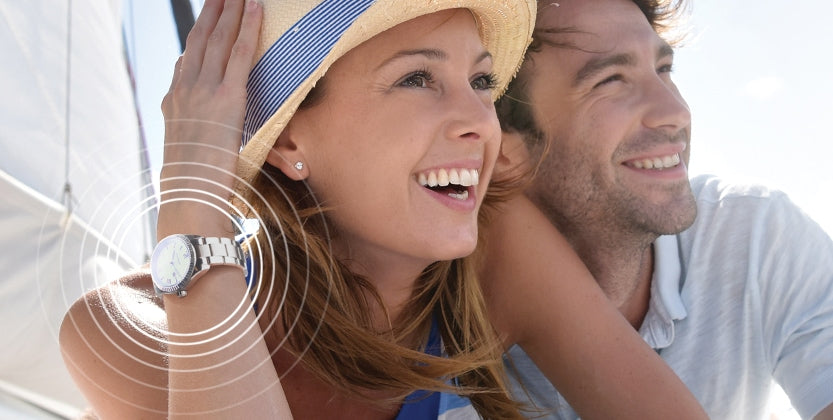 Woman wearing a Natural Frequency Technology watch sitting next to a man