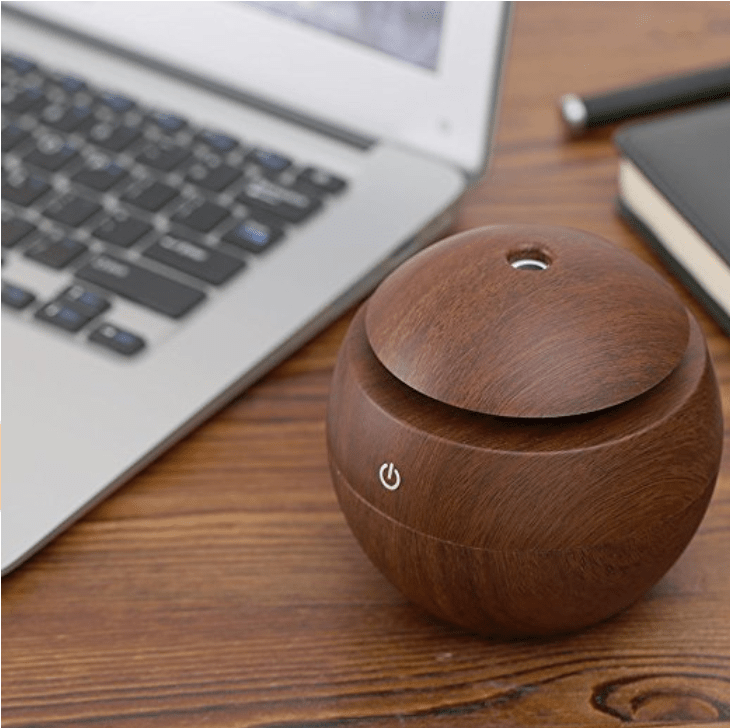 Wooden essential oil diffuser next to computer keyboard