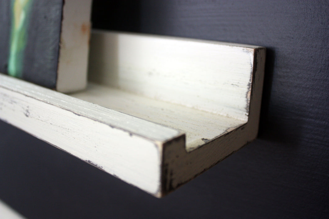 JTWoodworks white distressed ledge style shelf is perfect for organizing small items and displaying pictures or books within your home. It is also great in your office, studio, gallery or studio for displaying products and holding supplies.